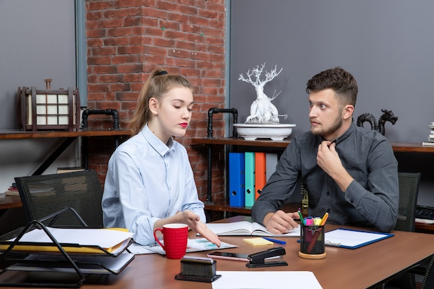 Вид сверху удивленного молодого человека и коллеги по работе, обсуждающих одну проблему в офисе