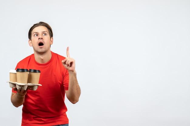 Вид сверху удивленного молодого человека в красной блузке, держащего заказы и указывающего вверх на белой стене