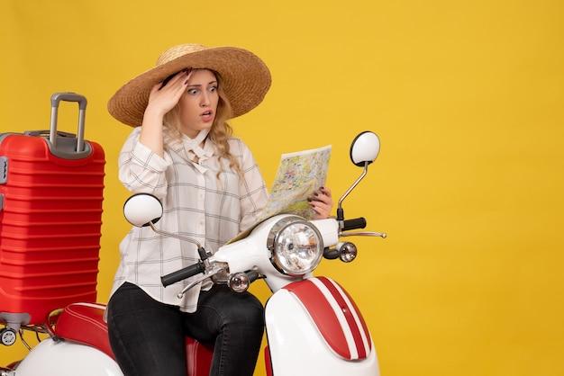 帽子をかぶってバイクに座って、黄色の地図に集中して驚いた若い女性の上面図