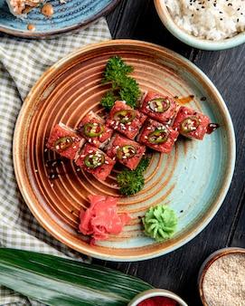 Вид сверху суши роллы с тунцом на тарелку с имбирем и васаби на деревянной поверхности