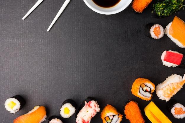 黒い背景、日本食、箸とソースとセット寿司のトップビュー。