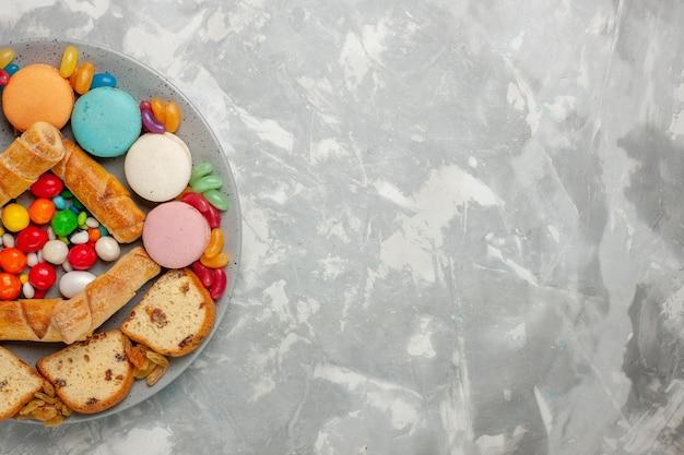 Вид сверху сладких рогаликов с кусочками торта, макарон и конфет на белой поверхности