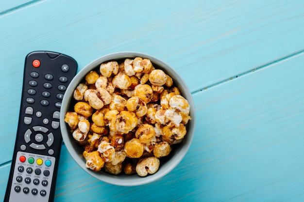 Вид сверху сладкого карамельного попкорна в миску и тв пульт на синем фоне