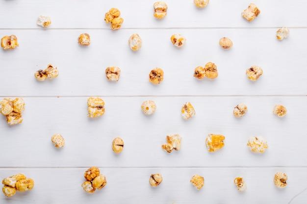 Вид сверху сладкого карамельного попкорна на белом фоне деревянные