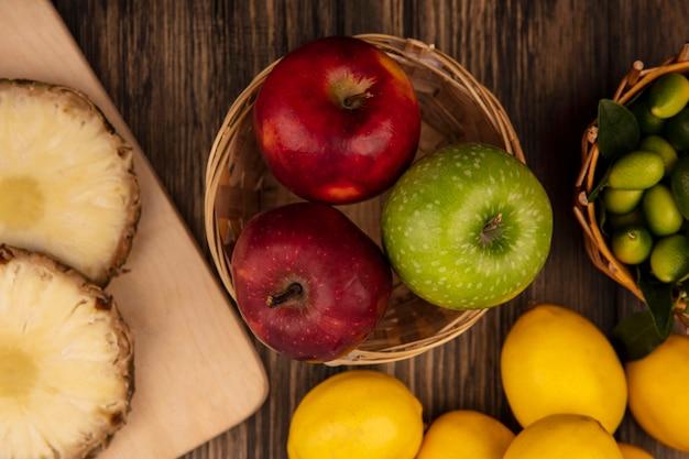 나무 표면에 고립 된 레몬 양동이에 kinkans와 나무 주방 보드에 파인애플과 양동이에 달콤한 다채로운 사과의 상위 뷰