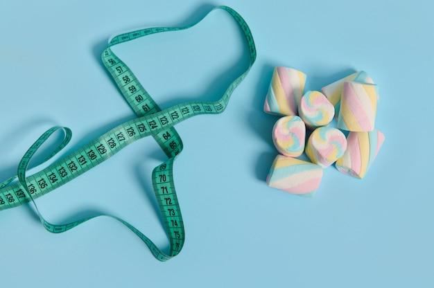 医療広告用のコピースペースと青い背景の甘いカラフルなマシュマロと巻尺の上面図。太りすぎと不健康な食生活の間のリンク。世界糖尿病デーのコンセプト