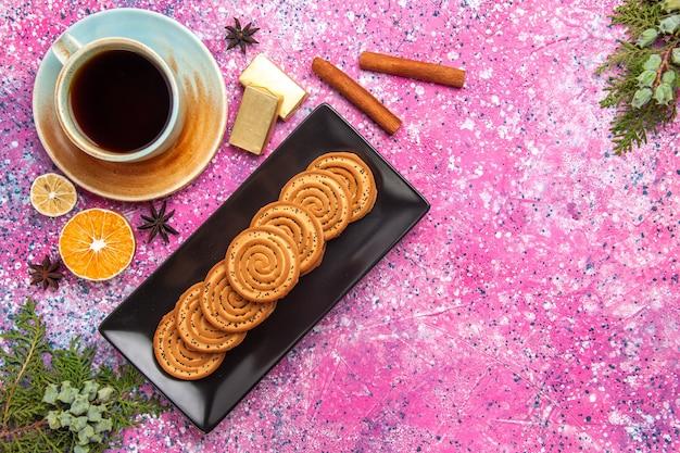 Вид сверху сладкого печенья внутри черной формы с корицей и чаем на светло-розовой поверхности