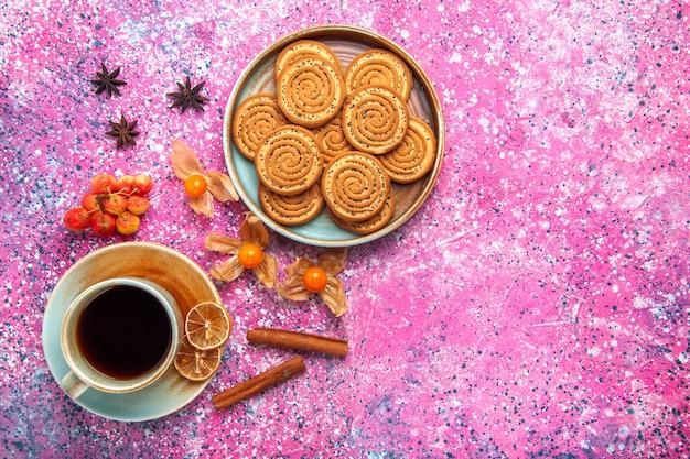 Вид сверху сладкого печенья внутри тарелки с чашкой чая и корицей на розовой поверхности