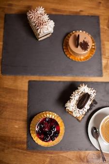 コーヒーショップで新鮮な果物と甘い装飾が施されたケーキの上面図。ホワイトクリームをのせた美味しいケーキ。おいしいビスケットのケーキ。
