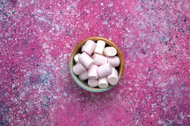 분홍색 표면에 둥근 냄비 안에 형성된 달콤한 맛있는 마시맬로의 상위 뷰