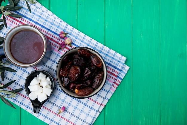 Вид сверху сладких сушеных фиников в миске с чашкой чая и кусочками сахара в блюдце на плед скатерть на зеленой древесине с копией пространства