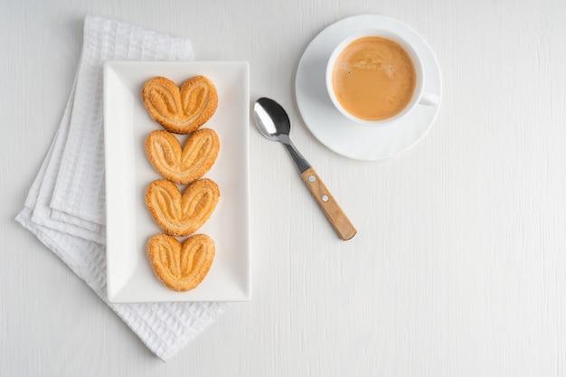 Вид сверху сладкого домашнего печенья в форме пальмового сердца на тарелке с чашкой кофе