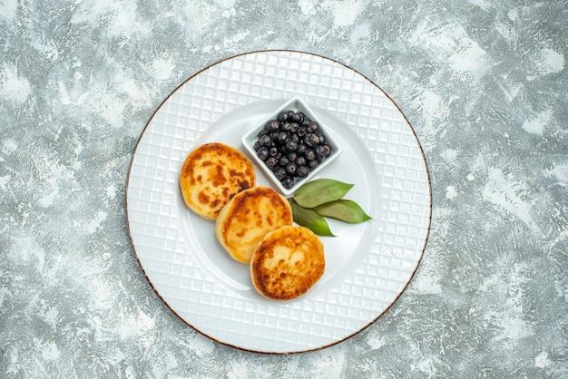 Вид сверху сладких кексов с ягодами внутри тарелки на светлой поверхности