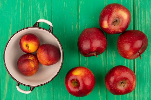 Вид сверху сладких персиков на миске с красными яблоками, изолированными на зеленой деревянной стене