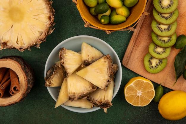 緑の背景に分離されたレモンとシナモンスティックとバケツにキンカンと木製のキッチンボードにキウイスライスとボウルに甘いパイナップルスライスの上面図