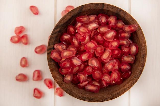 흰 나무 벽에 고립 된 씨앗과 나무 그릇에 달콤한 석류 씨앗의 상위 뷰