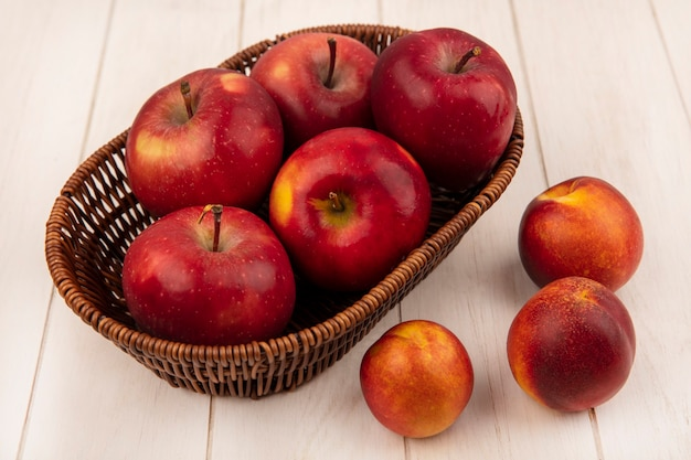 Вид сверху сладких красных яблок на ведре с персиками, изолированными на белой деревянной стене