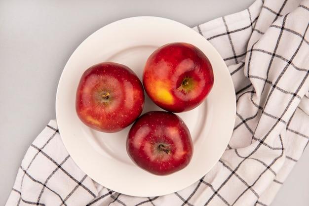 白い壁の上のチェックの布の上のプレート上の甘い赤いリンゴの上面図