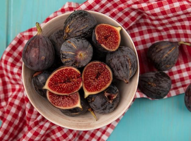 Вид сверху сладких спелых черных фиников на миске на красной клетчатой ткани на синей деревянной стене Бесплатные Фотографии
