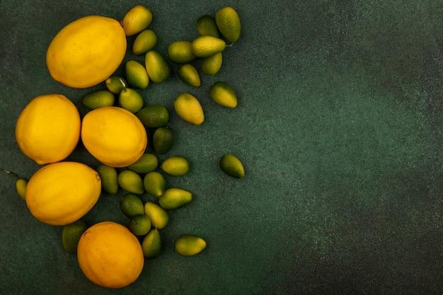 Вид сверху кисло-сладких кинканов с лимонами, изолированными на зеленом фоне с копией пространства