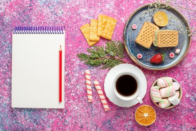 Вид сверху сладких вафель с чашкой чая на розовой поверхности