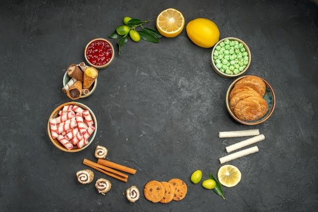 Вид сверху конфет, варенья из цитрусовых с листьями, конфет, печенья, выложенных по кругу