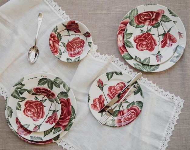 Вид сверху сервировки стола с тарелками с красочным цветочным узором