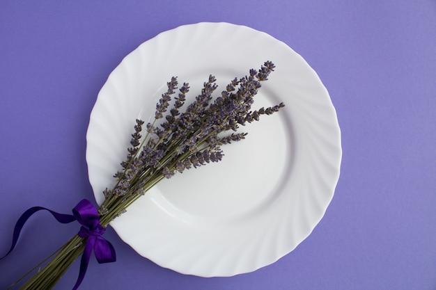 Вид сверху сервировки стола с белой тарелкой и сушеной лавандой