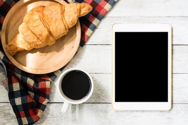 木製のテーブルの背景に、クロワッサンとコーヒーのタブレットのトップビュー。