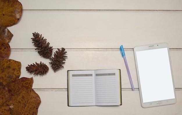 空の画面と白いテーブルの背景、フラットレイデザインのノートブックとタブレットの上面図