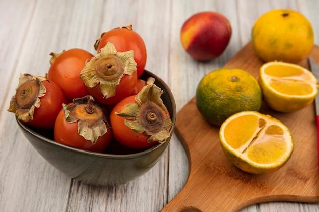 灰色の木製の壁に分離された桃とボウルに柿と木製のキッチンボード上のみかんの上面図