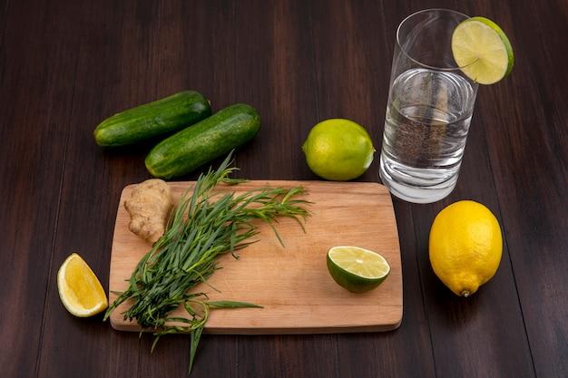 Взгляд сверху эстрагона на деревянной доске кухни с имбирем и лимонами с огурцом на деревянной поверхности