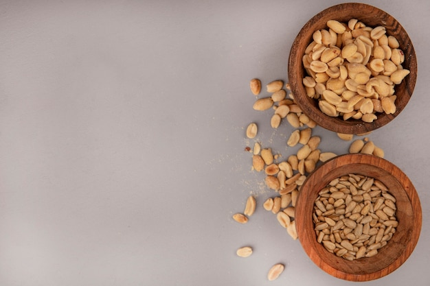 コピースペースで殻から取り出されたヒマワリの種と木製のボウルにおいしいと塩辛い松の実の上面図