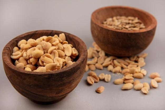 Вид сверху вкусных и соленых кедровых орехов на деревянной миске с очищенными семечками