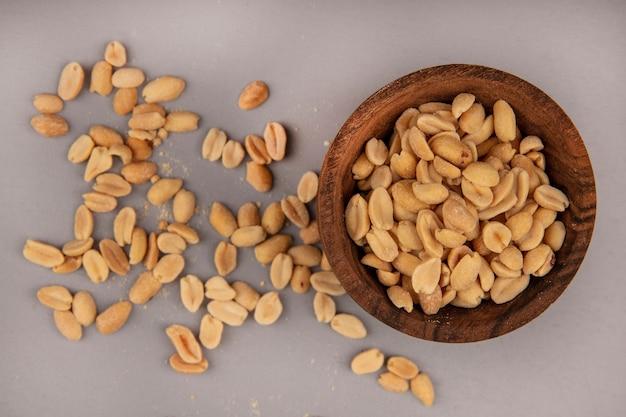 Вид сверху вкусных и соленых кедровых орехов на деревянной миске