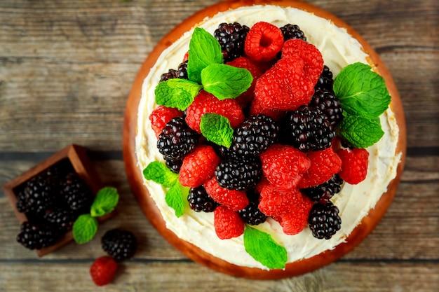 新鮮なラズベリーとブラックベリーで飾られたおいしいベリーケーキの上面図。閉じる。