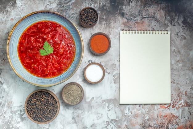 Вид сверху вкусного борща украинский свекольный суп с приправами на белой поверхности