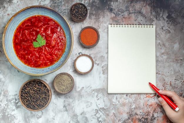 흰색 표면에 조미료와 함께 맛있는 보쉬 우크라이나 사탕 무우 수프의 상위 뷰