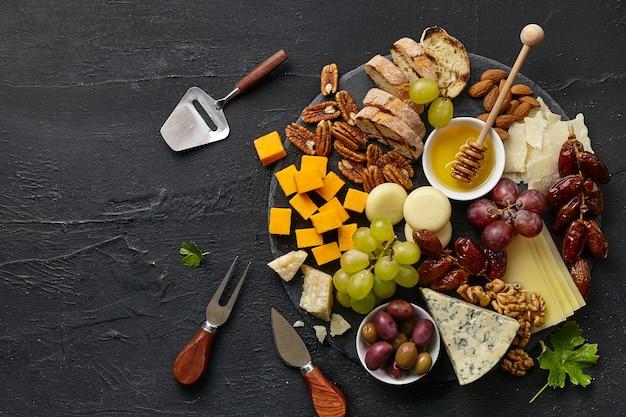 검은 돌 배경, 평면도, 복사 공간에 원형 주방 접시에 과일, 포도, 견과류와 꿀 맛있는 치즈 플레이트의 상위 뷰. 맛있는 음식과 음료.