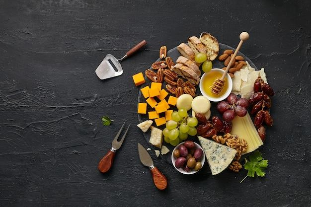 黒い石の背景に円のキッチン プレートに果物、ブドウ、ナッツ、蜂蜜を入れたおいしいチーズ プレートのトップ ビュー、トップ ビュー、コピー スペース。グルメフードとドリンク。