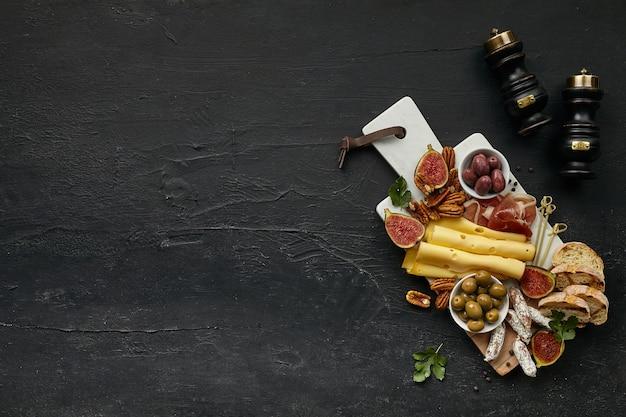 검은 돌 배경, 평면도, 복사 공간에 나무 주방 접시에 과일, 포도, 견과류, 올리브, 베이컨, 구운 빵과 함께 맛있는 치즈 플레이트의 상위 뷰. 맛있는 음식과 음료.