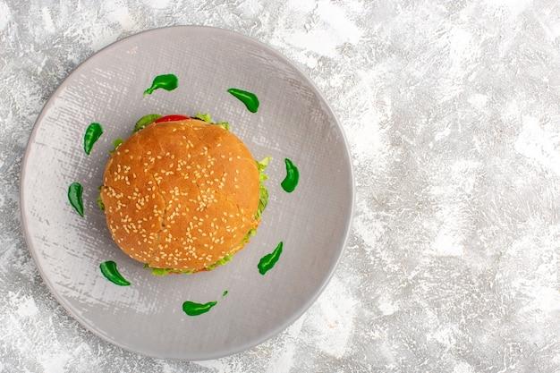白い表面のプレートの中にグリーンサラダと野菜とおいしいチキンサンドイッチの上面図