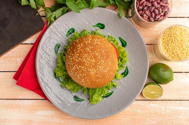 Вид сверху вкусного куриного сэндвича с зеленым салатом и овощами внутри тарелки на деревянной кремовой поверхности