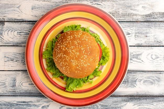 Вид сверху вкусного куриного сэндвича с зеленым салатом и овощами внутри тарелки на деревянной деревенской серой поверхности
