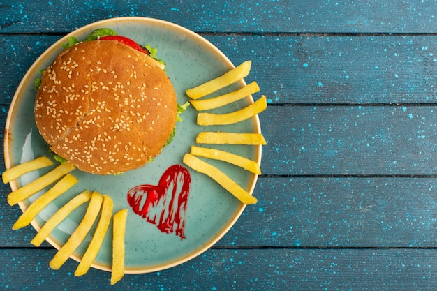Вид сверху вкусного куриного сэндвича с зеленым салатом и овощами внутри тарелки с картофелем фри на деревянной синей поверхности