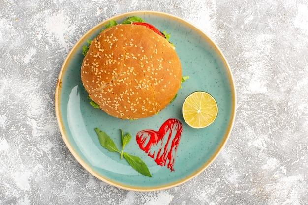 Вид сверху вкусного куриного сэндвича с зеленым салатом и овощами внутри тарелки с лимоном на светлой поверхности