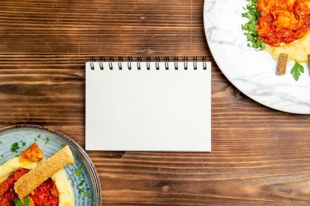 茶色の木製テーブルにマッシュポテトとおいしい鶏肉スライスの上面図