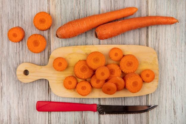 회색 나무 표면에 고립 된 당근 칼으로 나무 주방 보드에 맛있는 다진 당근의 상위 뷰