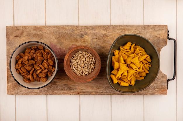ベージュの木製テーブルの上の木製のキッチンボード上の木製のボウルに殻から取り出されたヒマワリの種と小さなライ麦のラスクが付いているボウルにおいしい円錐形の揚げコーンスナックの上面図
