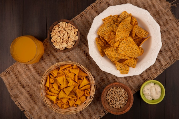 木製のテーブルにオレンジジュースのガラスと殻から取り出されたヒマワリの種と木製のボウルに松の実と袋布のバケツにおいしい円錐形の揚げコーンスナックの上面図
